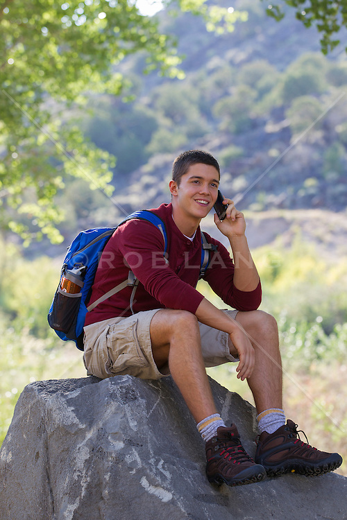 young man enjoying talking on the cell phone  while taking a break from a hike
