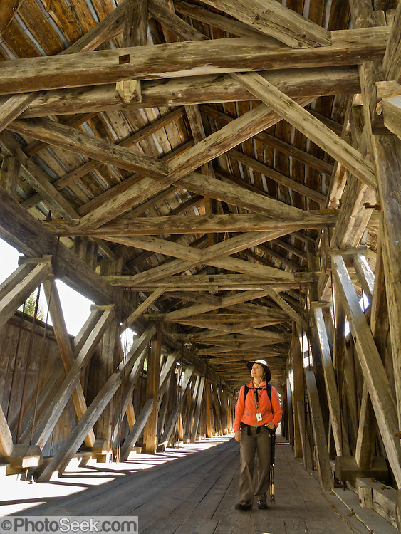 """Old wood timbers frame the covered bridge in Scuol (or Schuls, 1244 meters or 4081 feet elevation), in Graubünden canton, Switzerland, the Alps, Europe. Scuol is the terminal station of the """"Rätische Bahn"""" (RhB). The Swiss valley of Engadine translates as the """"garden of the En (or Inn) River"""" (Engadin in German, Engiadina in Romansh, Engadina in Italian)."""