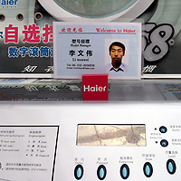 "QINGDAO, MARCH 2005: a portrait of the "" best worker"" is placed on a washing machine in the Hai'er showroom in Qingdao."