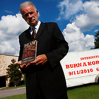 GAINESVILLE, FL -- August 18, 2010 -- Pastor Terry Jones poses for a portrait with a copy of his book at the Dove World Outreach Center in Gainesville, Fla., on Wednesday, August 18, 2010.  The church is planning on burning multiple copies of the Koran on the anniversary of the September 11th terrorist attacks.  (Chip Litherland for The New York Times)