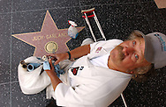 John Peterson pauses while cleaning the brass nameplates of the stars along the Walk of Fame on Hollywood Boulevard in Hollywood, CA on Thursday, July 29, 2004.