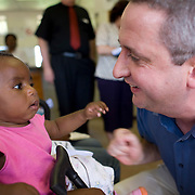 28 November 2008, Ivory Park, South Africa. Ivan Lewis, UK Minister for International Development, greets baby Daphyne Matlabyane at a clinic dispensing ARV drugs.