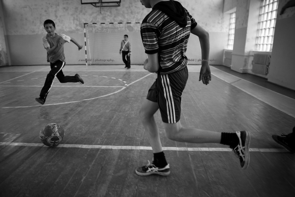 """Young group of soccers playing in Shushis new renovated sports hall. This image is part of the photoproject """"The Twentieth Spring"""", a portrait of caucasian town Shushi 20 years after its so called """"Liberation"""" by armenian fighters. In its more than two centuries old history Shushi was ruled by different powers like armeniens, persians, russian or aseris. In 1991 a fierce battle for Karabakhs independence from Azerbaijan began. During the breakdown of Sowjet Union armenians didn´t want to stay within the Republic of Azerbaijan anymore. 1992 armenians manage to takeover """"ancient armenian Shushi"""" and pushed out remained aseris forces which had operate a rocket base there. Since then Shushi became an """"armenian town"""" again. Today, 20 yeras after statement of Karabakhs independence Shushi tries to find it´s opportunities for it´s future. The less populated town is still affected by devastation and ruins by it´s violent history. Life is mostly a daily struggle for the inhabitants to get expenses covered, caused by a lack of jobs and almost no perspective for a sustainable economic development. Shushi depends on donations by diaspora armenians. On the other hand those donations have made it possible to rebuild a cultural centre, recover new asphalt roads and other infrastructure. 20 years after Shushis fall into armenian hands Babies get born and people won´t never be under aseris rule again. The bloody early 1990´s civil war has moved into the trenches of the frontline 20 kilometer away from Shushi where it stuck since 1994. The karabakh conflict is still not solved and could turn to an open war every day. Nonetheless life goes on on the south caucasian rocky tip above mountainious region of Karabakh where Shushi enthrones ever since centuries."""