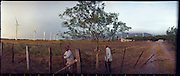 "Zapotec campesinos repair a fence on their land in La Venta, Oaxaca where foreign companies have placed windfarms. ..The Isthmus of Tehuantapec, long a center for indigenous land ownership, is now embroiled in a land dispute over wind farm land...Called ""Mexico's little waist,"" the Isthmus is a wind tunnel that links the Gulf of Mexico to the Pacific through mountain passes at the narrowest part of Mexico. The geographical funnel makes it one of the windiest places in North America and for a decade wind energy companies have been jostling to acquire land to power the likes of Coca-Cola and Wal Mart."