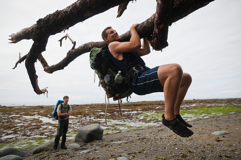 Henry does pull ups from a tree branch on the beach as Zach Podell-Eberhardt watches, West Coast Trail, British Columbia, Canada.