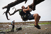 Henry Pedersen does pull ups from a tree branch on the beach as Zach Podell-Eberhardt watches, West Coast Trail, British Columbia, Canada.