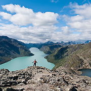 Besseggen is one of the most popular hikes in Norway. The mountain ridge of Besseggen (or Besseggi) rises between green Lake Gjende and blue lake Bessvatnet in Oppland county, in Jotunheimen (the Home of the Giants, the highest section of the Scandinavian Mountains), Norway. Ride a boat from Gjendesheim to Memurubu, then hike along the trail to narrow Besseggen at the halfway point. Then ascend to the trail's highest point, Veslfjellet (1743 meters), and walk steeply down to Gjendesheim, in about 8 to 10 hours total. Pretty Lake Gjende is colored green from glacier runoff containing clay (rock flour).