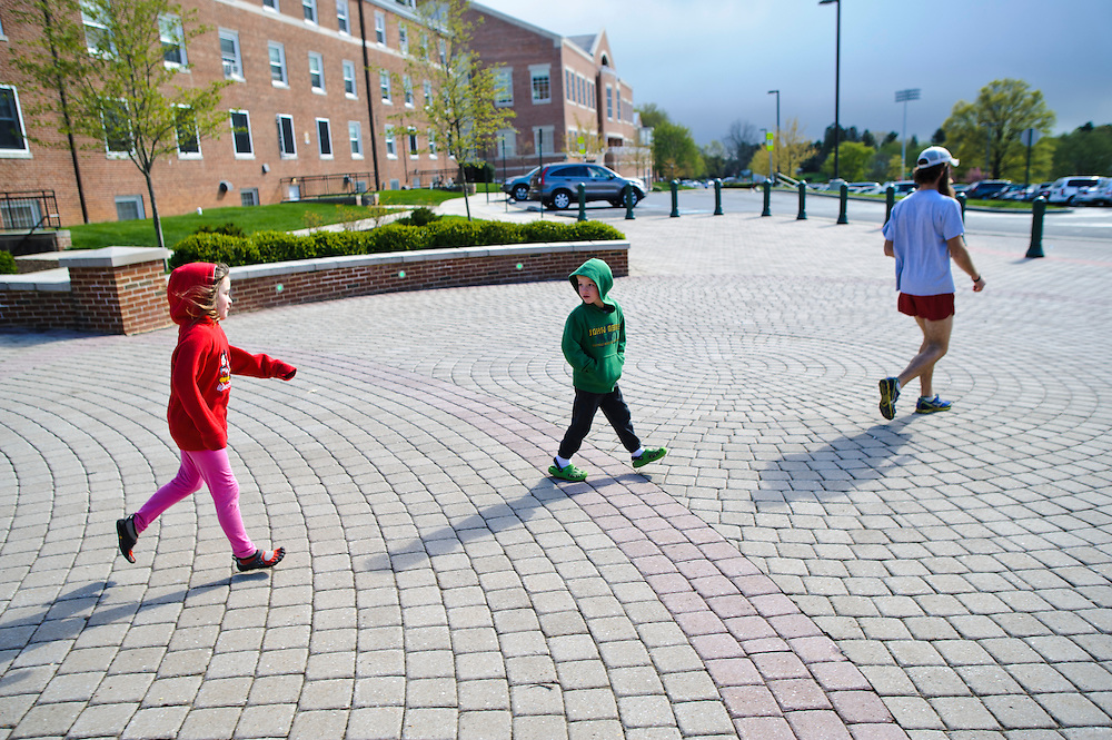 photo by Matt Roth.Wednesday, April 11, 2012..Ron Shriver leads his children Rory, left, and Miles, right, around McDaniel College, trying to figure out if track practice is going to be held outside on the track or, because of the looming storm clouds, indoors...Ron Shriver is a retired marine staff sergeant. He is also the first in his family to attend college, thanks to the New G.I. Bill. His wife, a fellow retired Marine, is finishing up graduate school in Alaska. After Ron gets his undergraduate degree from McDaniel College in May, he plans to drive to Alaska with is two children Rory, 6, and Miles, 5. For the move Ron got rid of most of his family's belongings, and after his lease was up, he and his children moved back into his parent's farmhouse.