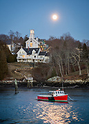 A full moon hangs over Rockport Harbor, casting a dazzling reflection in the water around the Becca & Meagan, a red lobster boat moored in the harbor. On the hill behind the boat are two large homes, one is an old church in the process of being renovated and added on to.