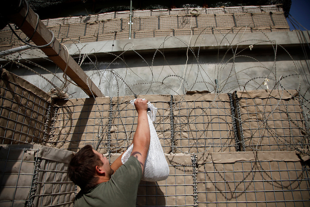 A german soldier tries to get an recently unloaded bag of fresh washed laundry hanging accidentially in the barbed wire at District Headquarters, Chahar Dareh.