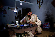 Tailors wait for customers at a workshop in the 'Old City' sector of Lahore. Parts of Pakistan are reportedly suffering 12-20-hours of electricity load shedding (power outages) per day. Many industries are suffering as a result of not being ale to use production machinery during load shedding and are unable meet deadlines for manufacture and delivery of goods.