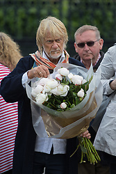 Parliament Square, Westminster, London, June 17th 2016. Following the murder of Jo Cox MP friends and members of the public lay flowers, light candles and leave notes of condolence and love in Parliament Square, opposite the House of Commons. PICTURED: A man prepares to place a bouquet of flowers.