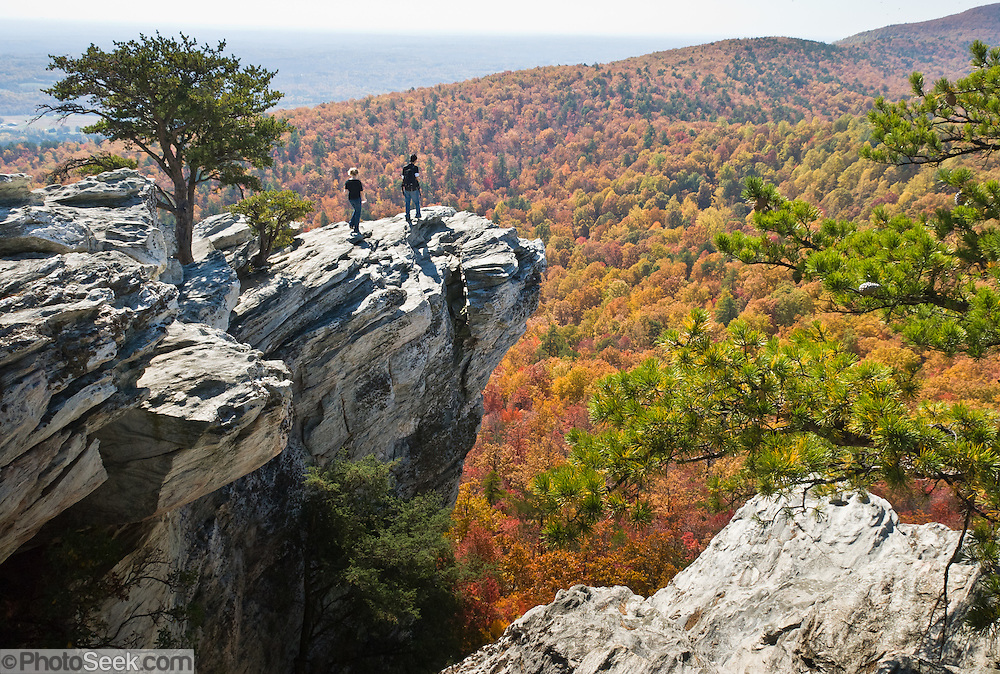 """Look across miles of autumn orange and red foliage at Hanging Rock State Park, Stokes County, North Carolina, USA. The eroded quartzite knob called Hanging Rock rises to 2150 feet elevation. The park is 30 miles (48 km) north of Winston-Salem, and approximately 2 miles (3.2 km) from Danbury. Hanging Rock State Park is located in the Sauratown Mountain Range, which is made up of monadnocks (or inselbergs, isolated hills) that are separated from the nearby Blue Ridge Mountains. Prominent peaks in the Sauratown range rise from 1,700 feet (520 m) to more than 2,500 feet (760 m) in elevation and stand in contrast to the surrounding countryside, which averages only 800 feet (240 m) in elevation. Named for the Saura Native Americans who were early inhabitants of the region, the Sauratown Mountains are the erosion-resistant quartzite remnants of mountains pushed up between 250 and 500 million years ago. Published in """"Light Travel: Photography on the Go"""" book by Tom Dempsey 2009, 2010."""