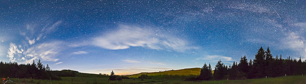A 180° panorama from northwest to east, taking in the Big Dipper, Polaris and Cassiopeia in the northern sky and the autumn constellations rising in the east, and the summer Milky Way overhead. Taken from the front yard of the Log Cabin at Reesor Ranch, July 16, 2013. This is a 5-section pan taken with the 14mm Samyang lens at f/2.8 for 40s each with the Canon 5D MkII at ISO 3200. Light from the setting waxing Moon provided the illumination to Earth and sky. Stitched with Photoshop. Two cameras taking time-lapses are at far left.