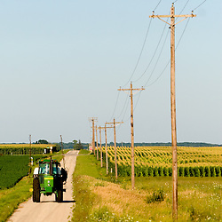 A John Deere tractor drives down a narrow country road towards the fields.