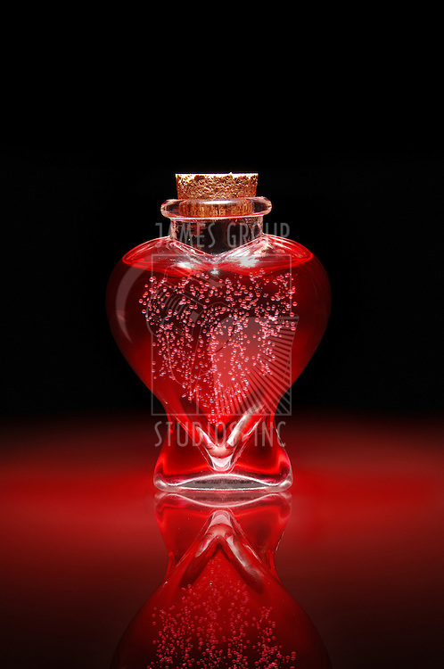Bottle of love potion shaped like a heart filled with bubbling red liquid