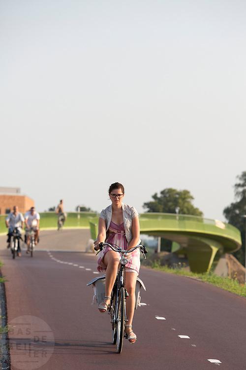 Een vrouw houdt haar rok vast tijdens het fietsen tegen het opwaaien waardoor je inkijk zou hebben. Bij Lent rijden fietsers over 't Groentje, de nieuwe fietsbrug die onderdeel is van het Rijn-Waalpad, de snelfietsroute tussen Arnhem en Nijmegen. Als de route helemaal klaar is, kunnen fietsers binnen 40 minuten van Arnhem naar Nijmegen fietsen. De snelfietsroute kent weinig obstakels en moet het aantrekkelijk maken om ook langere afstanden met de fiets af te leggen.<br /> <br /> Cyclists ride on 't Groentje (the little green), the new bike bridge which is part of the Rijn-Waalpad, the fast cycling route between Arnhem and Nijmegen. When the route is finished, cyclists can get within 40 minutes from Arnhem to Nijmegen. The fast cycle route has few obstacles and to make it attractive to commute long distances by bicycle.