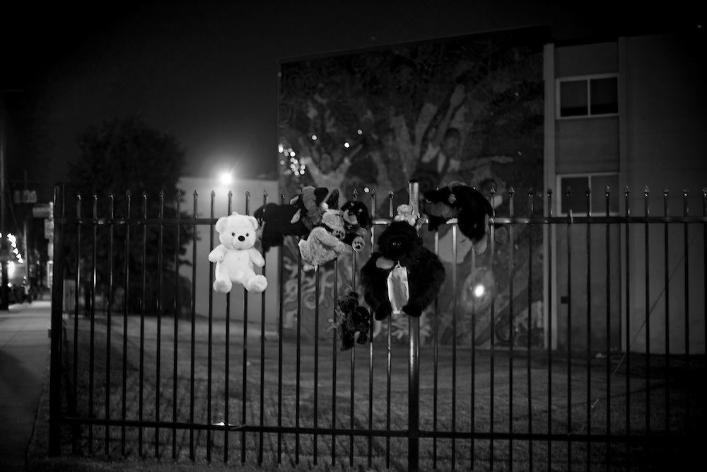 Street lights illuminate a teddy bear shrine that marks the corner where 14-year-old Deevon XXX lost his life to gun violence days before. Behind is a joyous mural children flying off into the sky.