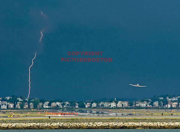 A small plane lands at Logan airport as a bolt of lightning strikes to it's north today, July 18, 2012. Staff photo by Mark Garfinkel