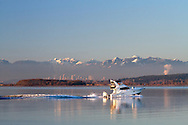 A small yacht passes Crescent Beach on Boundary Bay in Surrey, British Columbia.  City of Burnaby and the Northshore Mountains are in the background.  Photographed from Blackie Spit at Crescent Beach.