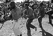 IPLM0013 , South Africa, Venda, June 2001. Male dancers blowing on homemade flutes or trumpets during a performance of traditional dance.