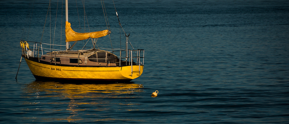 "Yellow ""Rag Doll"" sailboat floating on the Tamaki river mouth in the morning."