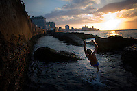 A child jumps into the sea along the Malecón in Havana, Cuba. ..With an aging Socialist dictatorship nearing it's end, Cuba is in a time of rapid change. Thedeteriorationis taking it's toll on the island nation as it remains locked in the Cold War eratime warp. As restrictions on Cuba's population are beginning to be lifted by the changing government, new hope is brewing in the minds of the the citizens as they hope for a future full of opportunity.. Photographer: Robert Caplin