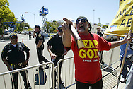 A man who called him self Bobby Bible waves his bible and yells at Michael Jackson fans with police looking on outside the courthouse where the jury in the Jackson case is deliberating in Santa Maria, California June 8, 2005. Jurors in Michael Jackson's sex abuse trial were resuming meeting as the pop star waited at his Neverland Valley Ranch for a verdict that could clear his name or brand him a convicted child molester.