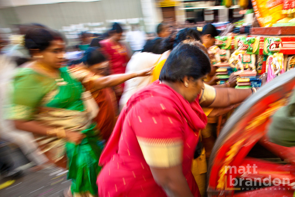 Women devotees follow the chariot on the way to Nattukotai Chettiar Temple.