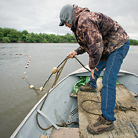 Henry Spein lets out a set net for subsistence fishing at fish camp, near Kwethluk, Alaska. With both ends anchored, the top of the set net is held by floats while the net sinks to the bottom. From his skiff Spein will pull fish from the nets later in the day.