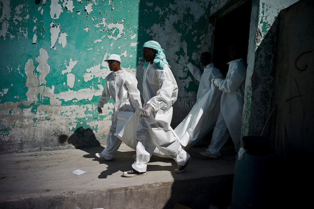 "Ten days before the presidential elections, Port-au-Prince continues to be affected by the cholera epidemic, the number of victims still increasing in the capital./// Employees of the NGO ""St Paul"", take away the body of a person died as a result of cholera, at the general hospital's morgue in Port-au-Prince."