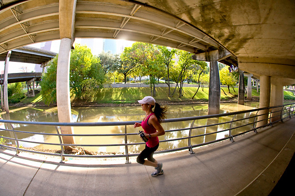 Woman jogging on a pathway along the water in Buffalo Bayou park in Houston, Texas