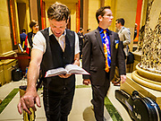 01 MAY 2017 - ST. PAUL, MN: JOHAN GALOO, left, who said he is running for mayor of Minneapolis, reads the bible in front of the Minnesota State Senate Chamber in the state capitol. About 300 people, representing immigrants' and workers' rights organizations, marched through the Minnesota State Capitol during a demonstration to mark May Day, International Workers' Day.      PHOTO BY JACK KURTZ
