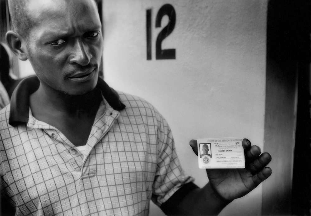 Timoter, a Haitian national who like many others has worked for years in the Dominican Republic without citizenship, holds a counterfeit registration card sold to him by a con man. Workers are frequently deported prior to receiving final payments and children are often denied access to education based on citizenship, Boca Chica, Dominican Republic.