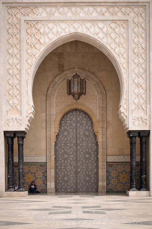 Morocco, Casablanca. Girl reading at the door of the Hassan II Mosque.
