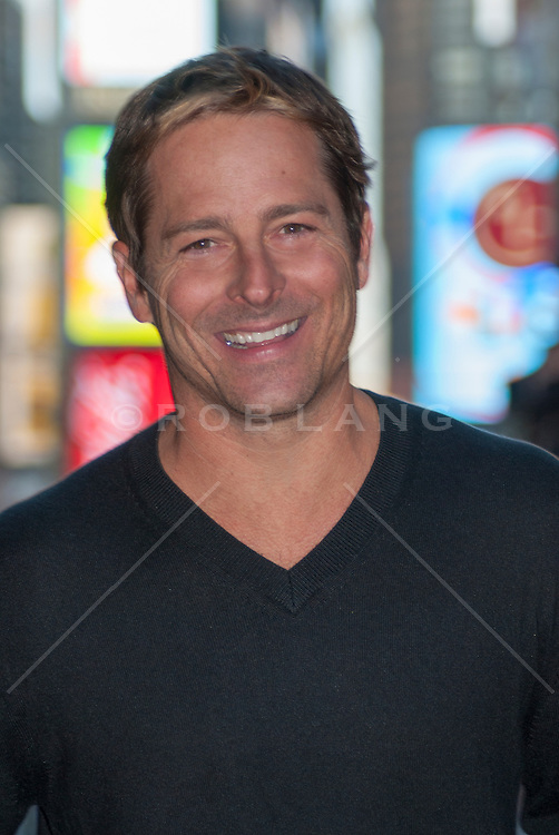 good looking thirty something year old man smiling outdoors in New York City at night