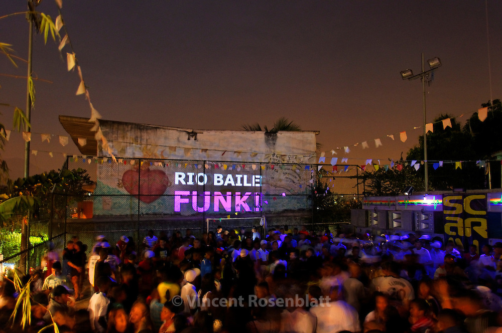 Baile Funk in the favela São João, in the district of Engenho Novo, Rio de Janeiro. On the wall, a slideshow of Vincent Rosenblatt's photos. After years documenting Baile Funk in the whole city - he started to show it back in the place where the work was done.
