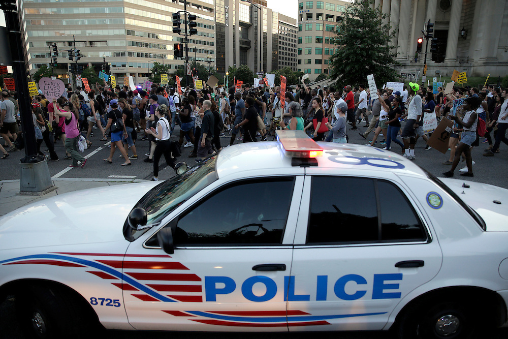 Demonstrators with Black Lives Matter march past a Metropolitan police officer blocking traffic during a protest in Washington, U.S., July 9, 2016.      REUTERS/Joshua Roberts