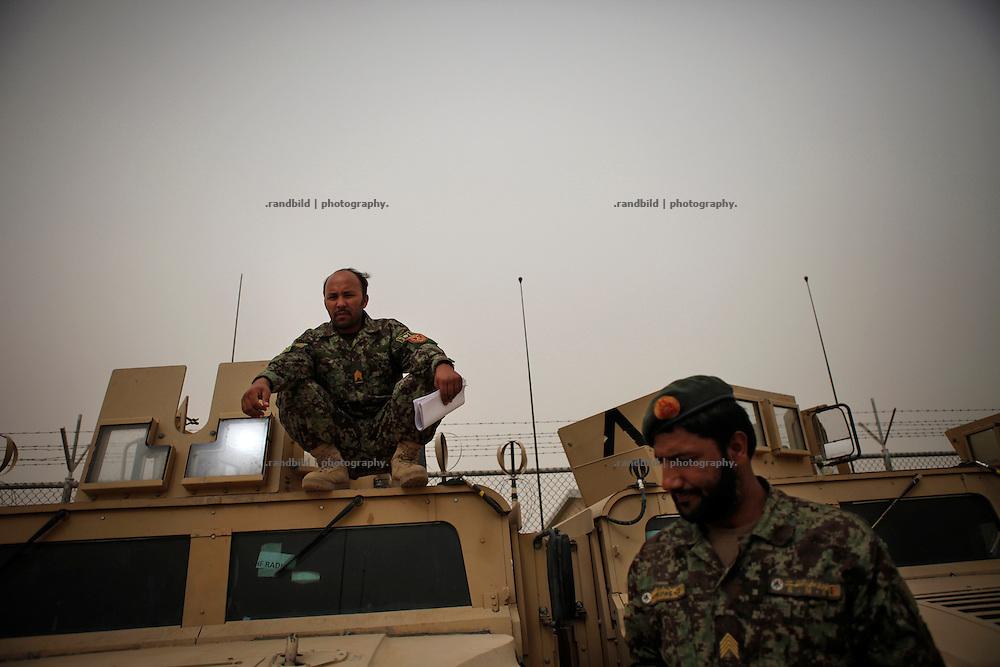 Afghan National Army members repair military vehicles at Camp Pamir carpark near Kunduz.