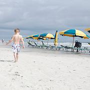 A small boy walks past a row of colorful beach umbrellas at the beach.
