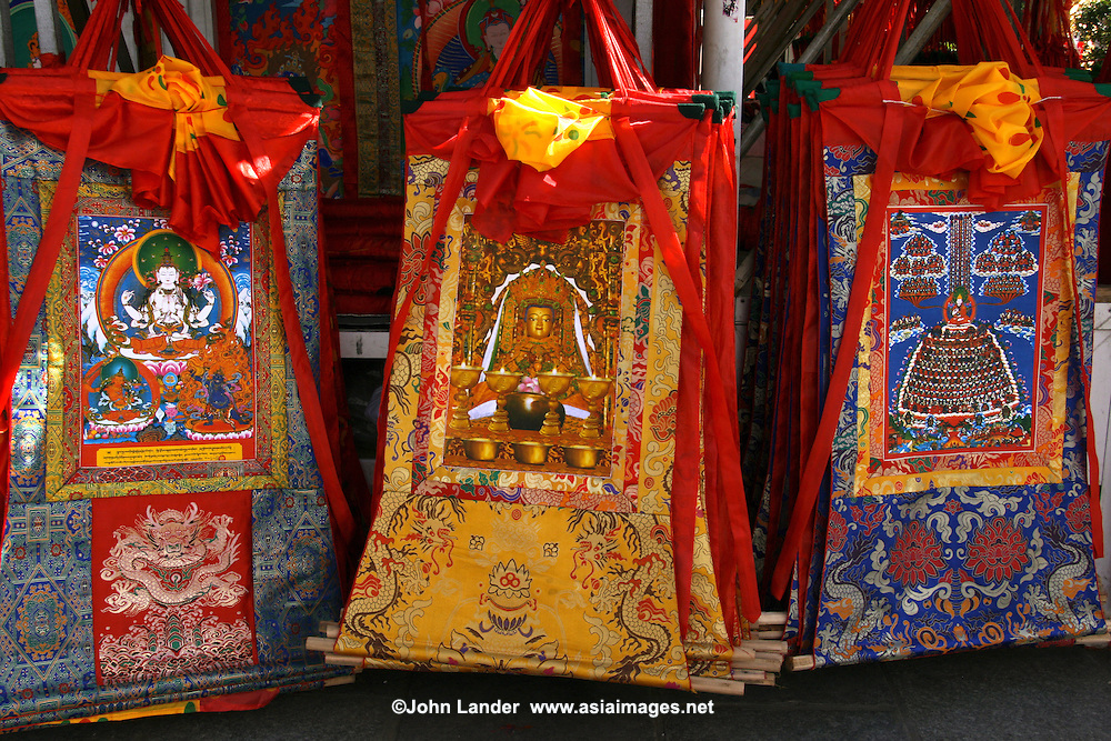 A thangka is a painted or embroidered Buddhist banner which is hung in a monastery or a family altar and occasionally carried by monks in ceremonial processions. Sometimes a thangka is called a scroll painting.  Originally, thangka painting became popular among traveling monks because the scroll paintings were easily rolled and transported from monastery to monastery. These thangka served as important teaching tools depicting the life of the Buddha, various influential lamas and other deities and bodhisattvas. One popular subject is The Wheel of Life.