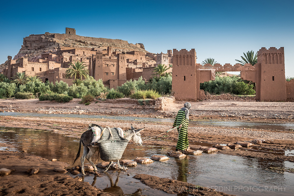 A woman pulls her donkey on a rudimental bridge crossing the stream in front of Aït Benhaddou old city (Ksar). This city, sited in Morocco, on the road from Marrakech to Sahara, has become famous for having staged several Hollywood blockbuster movies including the Gladiator and the Passion of Christ, and is protected by UNESCO as a world heritage site.