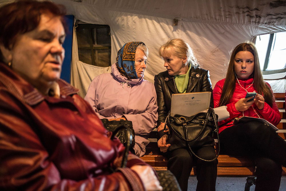 DNIPROPETROVSK, UKRAINE - OCTOBER 11: People wait in a tent for the opening of a center to help people displaced by fighting in Ukraine's East on October 11, 2014 in Dnipropetrovsk, Ukraine. The United Nations has registered more than 360,000 people who have been forced to leave their homes due to fighting in the East, though the true number is believed to be much higher. (Photo by Brendan Hoffman/Getty Images) *** Local Caption ***