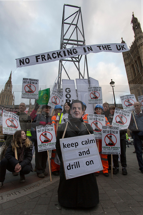 © licensed to London News Pictures. London, UK 01/12/2012. Protesters and a man wearing George Osborne mask posing in front of a 7.2 metre high fake ?fracking rig? outside parliament to protest against the expansion of hydraulic fracturing for shale gas into the UK Photo credit: Tolga Akmen/LNP