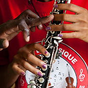 An instructor points out proper finger placement to a clarinet student.