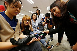 Curious students look at Aishah's bionic hand after she gave a talk about her life to students at Ngee Ann Polytechnic in Singapore 24 June 2014. One of Aishah's main occupation now is giving motivational talks where she shares her life and ordeal of overcoming her disability.