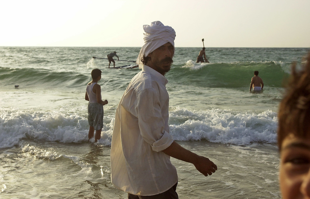 Palestinians enjoy the sea at the Gaza City beach on the Mediterranean coast as the sun goes down  July 2, 2000.