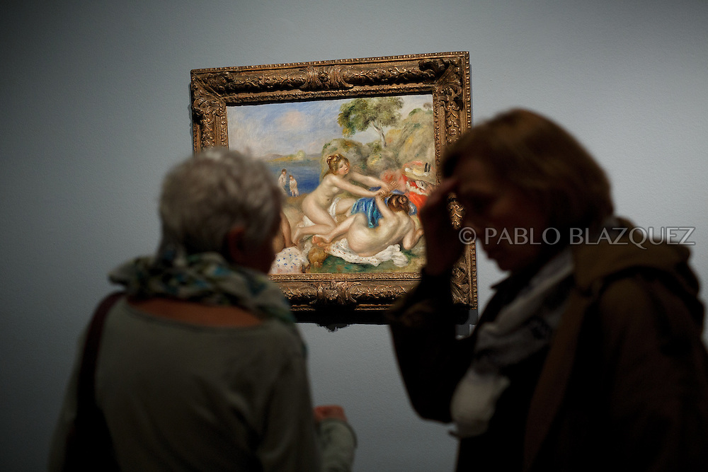 Members of the press look at Pierre Auguste-Renoir's work 'Bathers Playing with a crab', painted in 1897 at the Museum Thyssen-Bornemisza on October 17, 2016 in Madrid, Spain. 'Renoir: Intimacy' features 78 works by French painter Renoir (1841-1919) borrowed from museums and collections from around the world and will be open to the public from October 18, 2016 to January 22, 2017 (© Pablo Blazquez)