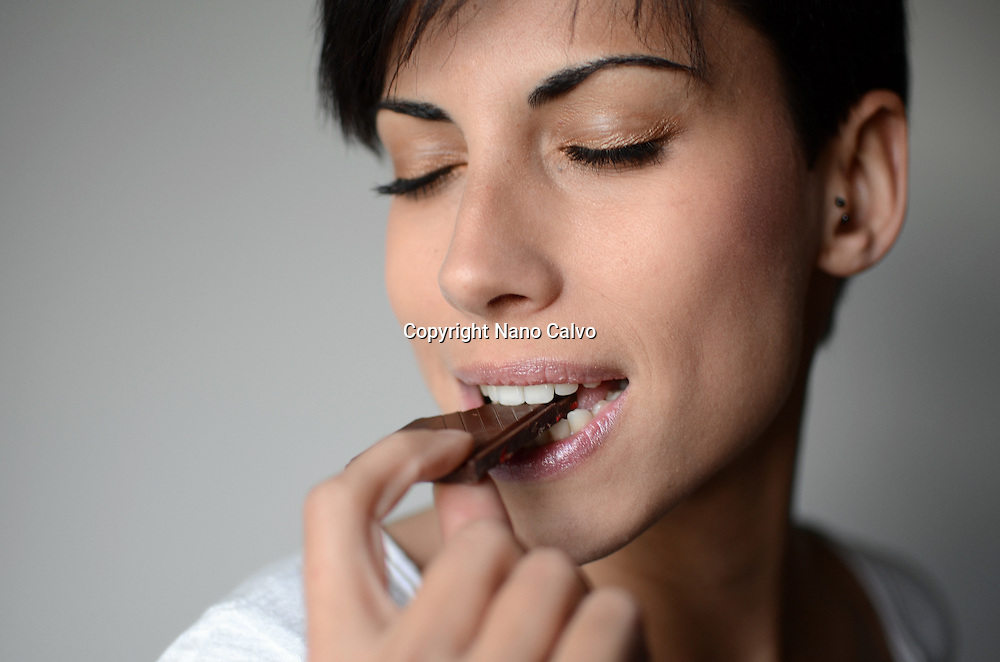 Young attractive woman eating chocolate