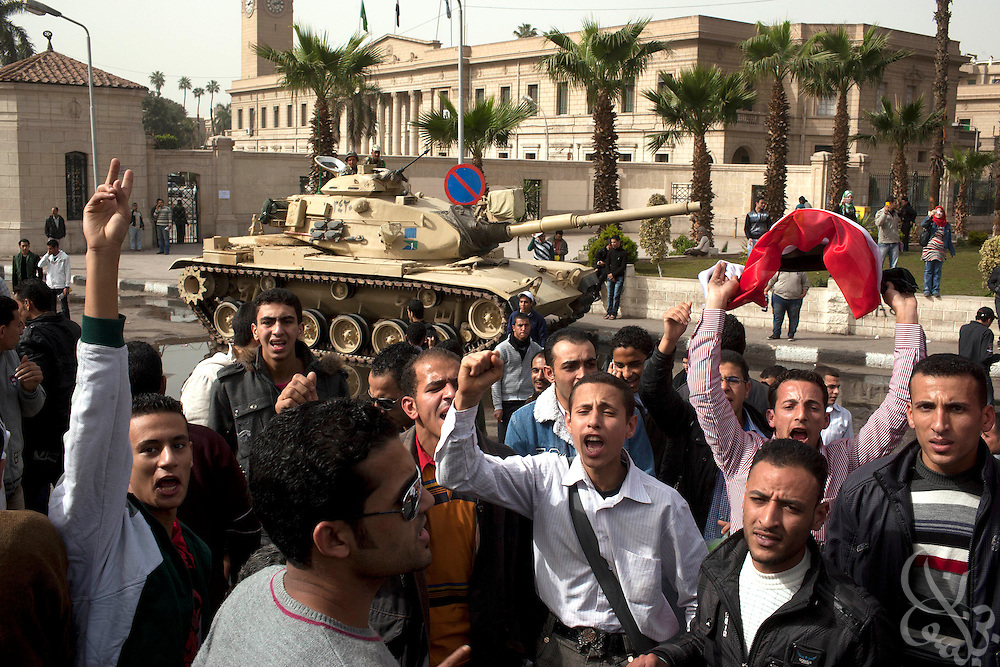 Egyptian men chant anti-government slogans near a military tank at the gates of Cairo University during ongoing protests January 28, 2001 in the Giza district of Cairo, Egypt January 29, 2011.  Egyptians traditionally have had more trust in the military as a professional and uncorrupted security force, and many are happy that it now has been deployed across Egypt in an attempt to calm tensions.